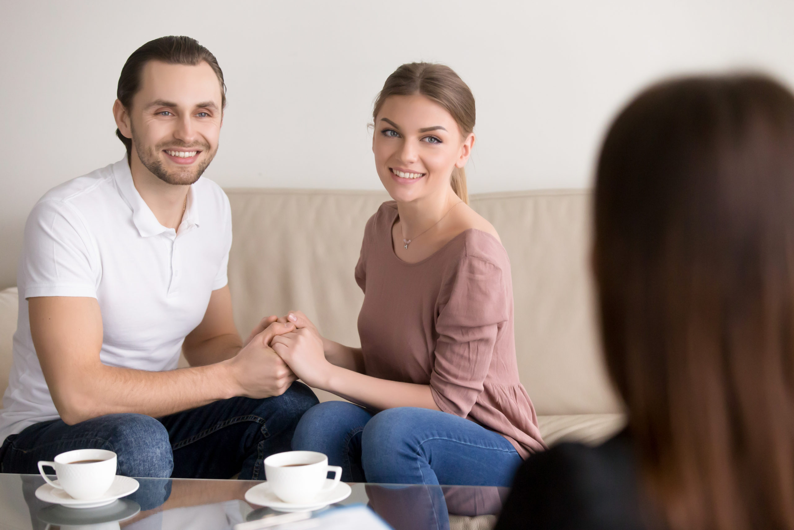 Happy young couple hold each other's hands listening to female agent, planning wedding, consulting investment advisor, hearing good news, casual marriage registration, buying real estate